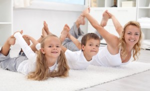 mom, kids stretching on floor