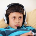 Young boy concentrating on playing video game with his friends with headset and microphone with copy space